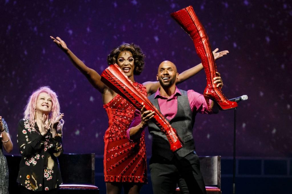 'Lola' Gino Emnes mit seinen »Kinky Boots«, im Hintergrund eine applaudierende Cyndi Lauper und J. Harrison Ghee, die sich mitfreuen.Foto: Stage Entertainment /Morris Mac Matzen